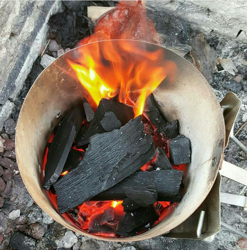 Lighting coals (such as lump charcoal seen here) in a chimney starter is a great way to go.