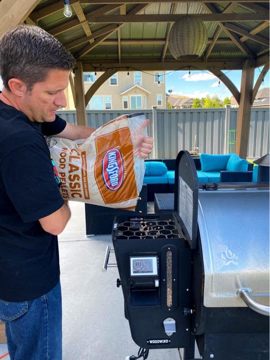 Pouring Kingsford wood pellets into the hopper of my pellet grill.